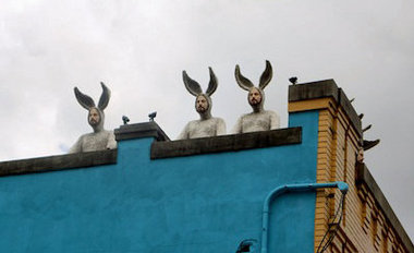 Three of Alex Podesta's 'bunny men' gaze down on Oretha Castle Haley Boulevard from their rooftop perch. (Photo: Linda Friedman)
