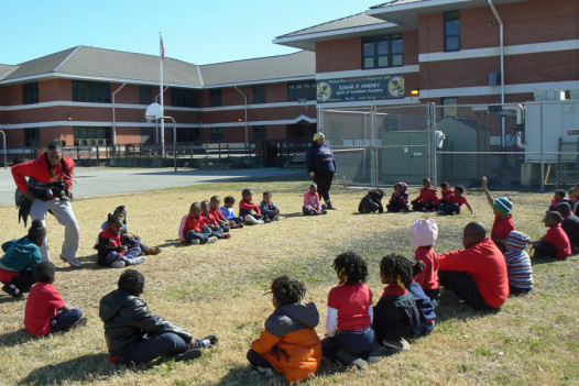 A group of students plays duck duck goose outside of Playworks.