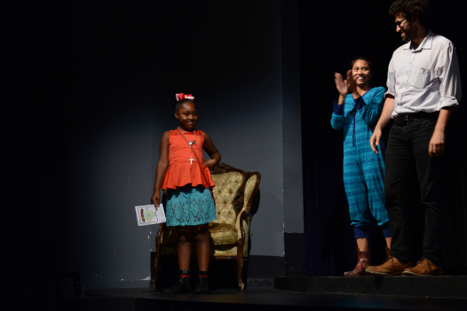 Paris Lynn Earin, a 2014 Play/Write student, watched her play from the side of the stage and receives applause.