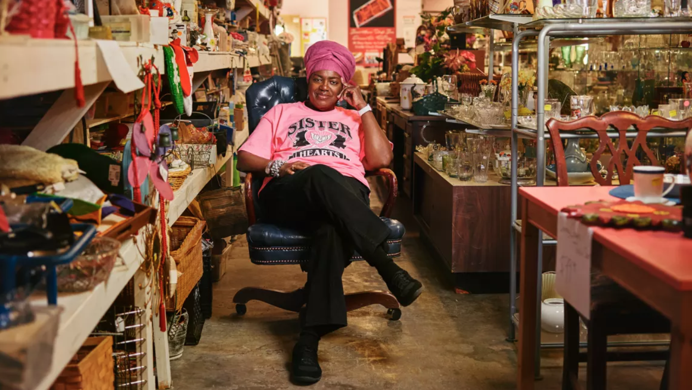 Ms. Maryam Henderson-Uloho, founder of Sister Hearts Thrift Store, sitting in her shop. Photo courtesy of Sister Hearts Thrift Store.